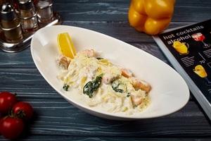 Локшина зі свіжим лососем, вершковим соусом і шпинатом
