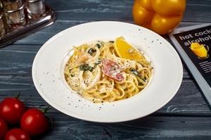 Спагетті з кальмаром, креветками та хрустким беконом у білому соусі