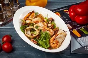 Велика тарілка зеленого салату з морепродуктами